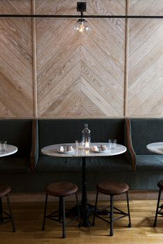 wood on wall, herringbone, panels, dark green banquette seating, stools, restaurant