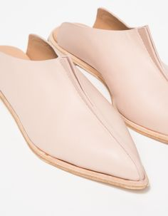 From Wal & Pai, a pair of slip on leather mules with modern falcon detail in nude.  Features pointed toe, pointed top falcon detail, painted edges, leather uppers, leather lining, leather outsole and small rubber heel.  • Slip on leather mules in nude