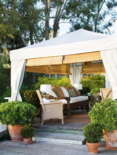 Weather-resistant fabric panels provide a romantic backdrop to this outdoor room, hiding the tent's structure and giving the space an intimate, enclosed feel. via BHG