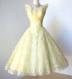 1950's Ceil Chapman crepe chiffon cocktail party dress, with two-layered asymmetrical bodice creatng a dramatic wrap around the shoulders, full four-layer skirt of lemon lace, yellow tulle, yellow underskirt, and a full and fluffy white crinoline. Crepe chiffon  waist wraps around and streams around the to the back of the dress.