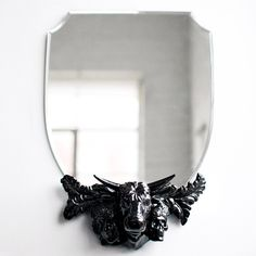 """Anchored in the centre by the head of a bull, the Mortality Mirror embodies this principle of balance: once cannot exist without the other. The bull's head is flanked on one side, by the face of a young girl, while the other displays a human skull. Adorned with a variety of flora, the Mortality Mirror will add the perfect amount of dark and light, to any wall. Designer: Flora Lam. Made of porcelain with a glass mirror. 18"""" x 4.5"""" x 12.5"""" Please allow 2-3 weeks for shipping."""