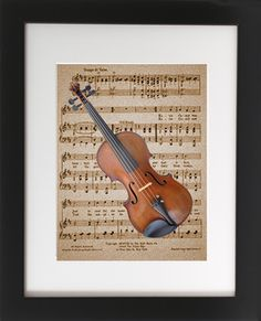 "Violin on Sheet Music. Matted with Wood Frame 8"" X 10"". This original art print produced exclusively by CherryPic Junction features a Classic Violin over Vintage Sheet Music. It is handmade in small production runs. The print comes in an 9"" X 11"" black wooden frame with white matting. The frame is ready to display in your home right out of the box! This is a dual purpose frame. You can choose to hang it on a wall or display it freestanding on a shelf, table or mantle. It's a beautiful…"