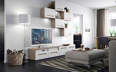 Salón con mueble para TV de nogal con cajones blancos y armarios de pared con puertas blancas; acabado con un reposapiés gris claro con patas cromadas.