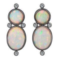 Australian White Opal Diamond Silver Gold Earrings. This pair of sensuously shaped Australian white opal earrings possess an incredible flashing luminescence which change color as they move, giving them an aura of both magic and mystery. Bezel set in 18 karat yellow gold and burnished silver, the cabochon opals weigh a total of 24.83 carats and are accented with mine cut diamonds which weigh 1.18 carats. Being an October birthstone, the rare stones are a perfect gift for a Libra or Scorpio or fo