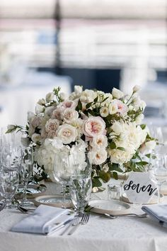 Classic pink and white roses table centerpiece. Find your florist at WeddingWire!