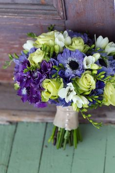 bouquets of dark purple hydrangeas, lime green roses, white anemones and feathers wrapped in dark blue ribbon with gold pins.