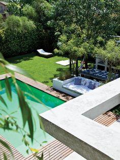 Ideas para una casa en un country: pérgolas y sillones en el jardín crean espacios de descanso al refugio del sol.