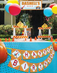 A Bright and Bold Construction Party with dump truck and tractor cookies, a chocolate dirt cake, cardboard bulldozer and wrecking ball, kid's dig zone + personalized hard hats