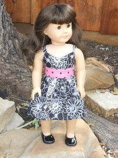 The main dress is black with white flowers and a pink with black polka dot middle. The dress closes in the back with Velcro.