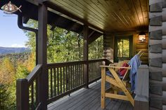 This alluring Blue Ridge Mountain view is enjoyed best from the high rise chairs on this front porch. Note the d-logs with dovetail corners and the equestrian theme light fixture.