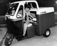 """1955 City letter carrier seated in a three-wheeled """"mailster"""" motor vehicle. Carriers used these vehicles to carry the ever-increasing amounts of mail that was being delivered to American households after end of the Second World War. Us Postal Service, United States Postal Service, Boutique Hotel Madrid, Moto Scooter, Mail Delivery, Going Postal, Car Wheels, Post Office, Inventions"""