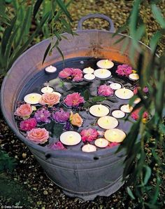 This water bucket filled with floating candles and flowers is a unique decoration for your backyard bash.