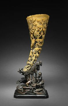 A carved rhinoceros horn with landscape and figural decoration, 19th century