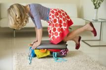Woman struggles to close suitcase full of clothes - Andrew Bret Wallis/Photographer's Choice RF/Getty Images