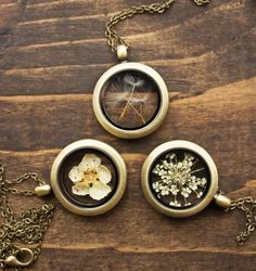 """Which one would you like to have?   Elegant botanical keepsake lockets made with a choice of dainty little flowers encased in glass to carry with you wherever you go! You have a choice of dandelion seeds (wishes!), Queen Annes lace and a single Hawthorne flower gathered from the hedgerows last Spring. - Find more beautiful pieces here: www.rubyrobinboutique.etsy.com"""