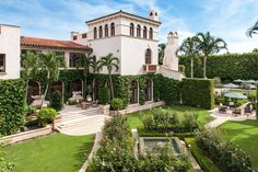This Pal Beach mansion has stucco walls, Spanish tile roofing, arched openings, an outdoor patio space, multiple chimneys, palm trees and manicured lawns.