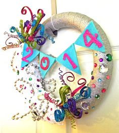 50% OFF SALE. Was $50.00 NOW $25.00.    Bring in the new year with this one of a kind piece. This 14 wreath is wrapped in a sparkly silver ribbon. Tons of white handmade flowers cover the piece along with crystals in an array of jewel tones. Spunky and colorful spiral picks are whimsically arranged while a felt banner drapes across the center with the numbers 2014 to represent a new year and a new beginning. Perfect for your home, special occasion, or gift!    **This item is OOAK (One of a…
