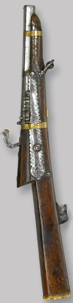 Indian tamancha torador (matchlock pistol), 18th to 19th century, 6 1/2 inch tapered two-stage barrel in .42 caliber smoothbore brass pin fore-sight; molded girdle retaining most of it's brass sheathing; breech section with integral rear sight; scalloped pan with swiveling cover. Barrel retained by two brass bands. Wooden stock of typical form, the iron sideplates with punched decoration; staghorn buttplate.