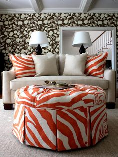 This contemporary living room blends funky pattern and color for an exciting contrast. Brown floral wallpaper provides a backdrop for the neutral sofa, orange zebra-print ottoman, and matching throw pillows. Round Storage Ottoman, Round Ottoman, Tufted Ottoman, Ottoman Table, White Ottoman, Table Lamps, Living Room Red, Living Spaces, Decoration Home