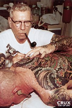 """Norman """"Sailor Jerry"""" Collins  American Traditional Tattoos.... umm awesome photo. this dude is so relaxed about giving tattoos that he is literally nonchalantly smoking."""