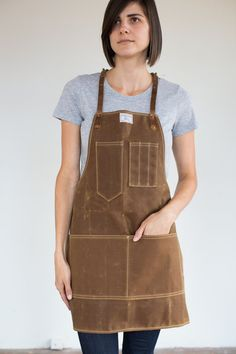 A traditional unisex work apron with adjustable leather neck and waist strap.  Sizing (Measure over clothing)  XS: Waist 24-28 / Hip 32-35 • Apron 26.5L x 23.5W  SM: Waist 28-32 / Hip 37-43 • Apron 27.5L x 26W  MED: Waist 32-38 / Hip 37-43 • Apron 29L x 29.5W  LG: Waist 38-44 / Hip 43-50 • Apron 31.5L x 31.5W  Materials  Rust Waxed Canvas Horween leather Hand hammered copper rivets Solid brass hardware Shuttle loomed taffeta label Mil-Spec poly thread  Its the best apron Ive owned. And Ive…