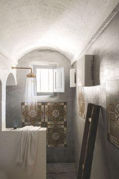 D'authentiques carreaux de ciment, récupérés sur le chantier, ont été sertis dans les murs en béton lissé de la salle de bains, en guise de décoration.