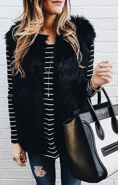 Black faux fur vest over black and white striped top with blue jeans. Love the chic handbag.