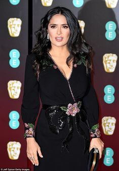 Added sparkle: Salma Hayek injected colour into her figure-hugging black gown with a pink ...