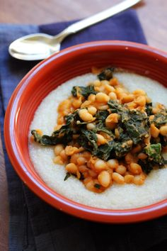 Spicy Cajun white beans and kale are served atop a bowl of creamy grits for a meatless meal that's big on bold flavor.