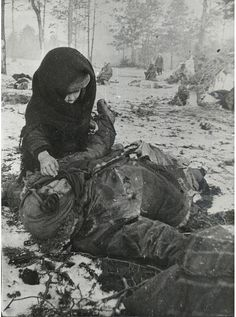 March 1944: A child in the Ozarichy hostage holding camp tries to wake up his mother, who has been murdered by the Germans. Ozarichy in Kalinkovichy region of Belarus was large fenced-in area on the German front line holding local civilians as human shields against Soviet attacks. The hostages were left without shelter, food, and water and were decimated by exposure, gunfire, and hunger. When Soviet troops finally defeated the Germans in the area, they found 15,960 children among the hostages.