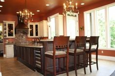 Red kitchen, with large island, concrete countertops, copper sinks, wine cooler, chandeliers, and paneled appliances.