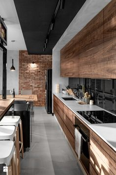 Create the look by using a gloss rectangular tile, plus a brick look-a-like tile. The red undertones in the brick and timber cupboards will offset the glossy black.