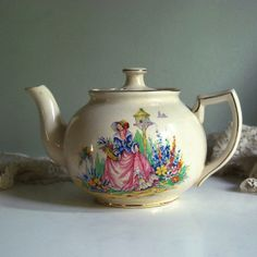 Sweet English teapot made by Arthur Wood between 1934 and 1945, decorated with a colorful garden scene.