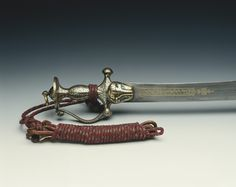 Talwar; blued steel hilt with scrolling knucklebow, flat disc pommel with swivel, short crossguard above tiger head langet with blade in its mouth; gilt inscriptions; back-edged curved steel blade with gilt inscription; green velvet covered scabbard.The sword belonged to Tipu Sultan (1750-99), the so-called Tiger of Mysore. Tipu Sultan succeeded as ruler of the South Indian state of Mysore in 1782, where he built a sophisticated and modern court around his palace at Seringapatam. He spent…