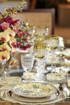 Na mesa da nossa sala de jantar, substituímos a toalha branca por jogos americanos rendados amarelos, e o sousplat da Coleção Petrópolis por sousplats em prata.