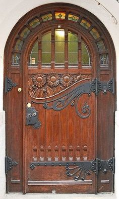 Carved door with round top and wrought iron hinges