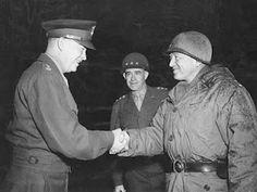 Gen. Eisenhower shaking hands with Gen. George Patton. Gen. Omar Bradley in background.
