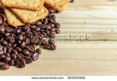 coffee beans and sweet biscuits on a wooden table with warm fall colors, soft-focus in the background. over light