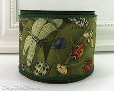 """Dragonflies, ladybugs, flies and bugs galore flit across the dark green cotton ribbon, 2 1/2"""" wide, with a medium weight wired edge covered in green thread. From the Cottage Crafts Online shop on Etsy."""