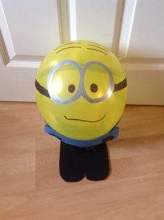 """The 5 year old had a yellow balloon in a party bag which sparked off an idea to Minionise it.  We used a black and a silver marker pen and an little blue tissue paper to make the Minion balloon. We mounted it onto some black card """"feet"""" but you could easily do without if filling with helium."""