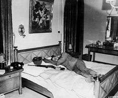 An American soldier taking a nap on bed belonging to German General Hermann Goering after elements of the US 3rd Army captured his lodge. Germany, 1945.