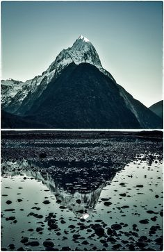 If visiting Milford Sound, one great piece of advice is not to go all the way to the water's edge at low tide. Some of the best shots are from the still reflection shots of the puddles that form from the retreating water. There are hundreds of these little pools. Some are clear without rocks and others have rocks. I decided to move around until I found a nice sequence of them. - Milford Sound, New Zealand - - Photo from #treyratcliff Trey Ratcliff at http://www.StuckInCustoms.com