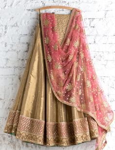 Buy this net golden lehenga choli with conscientious embroidery & lace work.This set is features a golden color blouse in silk fully embellished with foil booty work.It has matching golden lehenga in net with beautiful embroidery all over and pink dup Gold Lehenga, Indian Lehenga, Lehenga Choli, Sarees, Bridal Lehenga, Sharara, Khada Dupatta, Patiala Salwar, Lehenga Saree