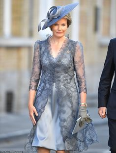 Queen Mathilde dazzled in a silk grey dress with a lace overlay, teamed with grey suede gl...