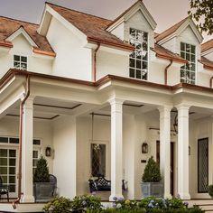 Nothing quite adds charm to a home like a big front porch. #foxgroupconstruction #frontporch #porchswing #copperraingutters #ipeflooring #cofferedceilings #paintedwhitebrick #cedarroof #columns #design #customhome #home #homedecor