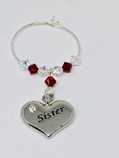 Sister Garnet Wine Glass Charm - set with a silver plated heart engraved with Sister - finished with Garnet and Clear Swarovski Crystals Garnet is the birthstone for January Wine Glass Charms, Organza Bags, Heart Charm, Birthstones, Garnet, Silver Plate, Swarovski Crystals, January, Bubbles