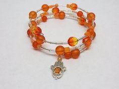 Floating orange bead memory wire bracelet with silver Hamsa charm.  by MyCreativeSideJewels