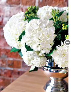 White hydrangeas pillowing out of a polished silver bowl create a brilliant contrast against an industrial backdrop, such as red brick. The large blooms soften the space while the polished silver adds that hint of glam.