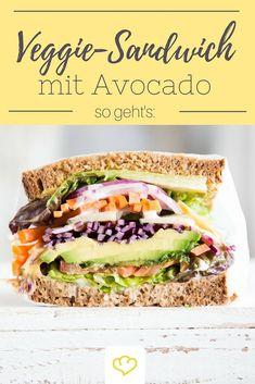 """Wow, was für ein Ding. Diese knackige, vegetarische Schlemmerei trägt den Namen """"Sandwich"""" wirklich zu Recht! Schicht für Schicht türmen sich Salat, Karotte, Gurke, Avocado und Co., eingerahmt von zwei saftigen Brotscheiben, so hoch, dass einem schon beim bloßen Anblick beinahe schwindelig wird.  Na, wer schafft es, alle 11 Schichten auf einmal, mit nur einem Bissen zu erwischen?!"""