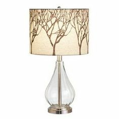 """Glass table lamp with a drum shade and tree branch silhouettes.  Product: Table lampConstruction Material: Metal, glass and fabricColor: Clear, champagne and tanAccommodates: (1) Bulb - not includedDimensions: 21.5"""" H x 12.5"""" Diameter"""